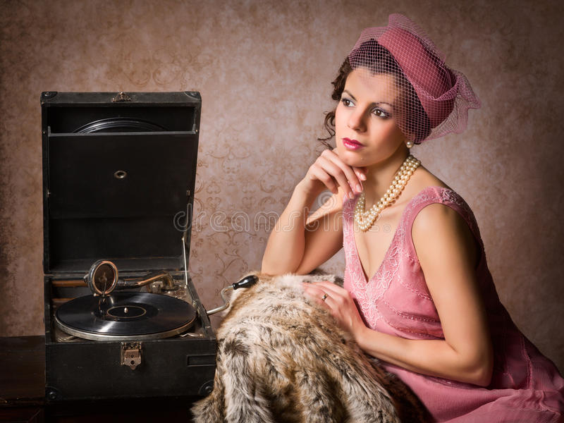 Vintage woman and record player. Vintage 1920s style lady in pink listening to an antique record player stock image