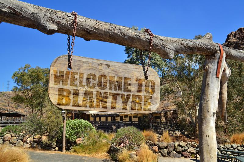 Vintage wood signboard with text welcome to Blantyre. hanging on a branch. Old vintage wood signboard with text welcome to Blantyre. hanging on a branch stock photo