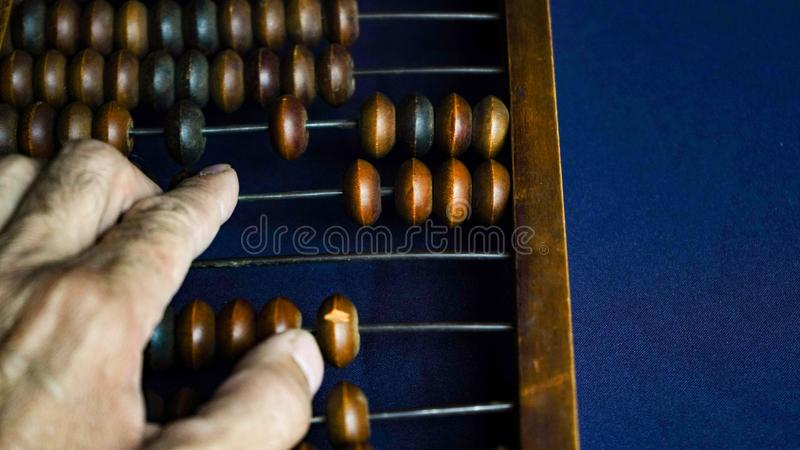 Vintage wooden abacus close up. A man s hand moves wooden knuckles on the bills. Part of the old end of the abacus on a dark blue. Background royalty free stock image