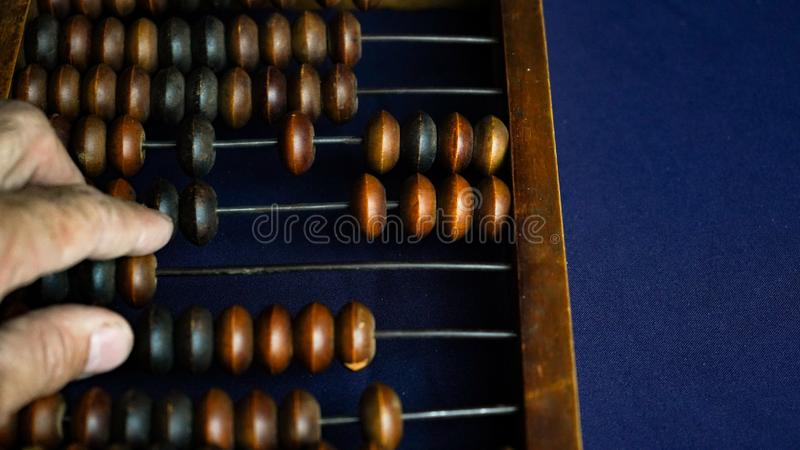 Vintage wooden abacus close up. A man s hand moves wooden knuckles on the bills. Part of the old end of the abacus on a dark blue. Background royalty free stock photography