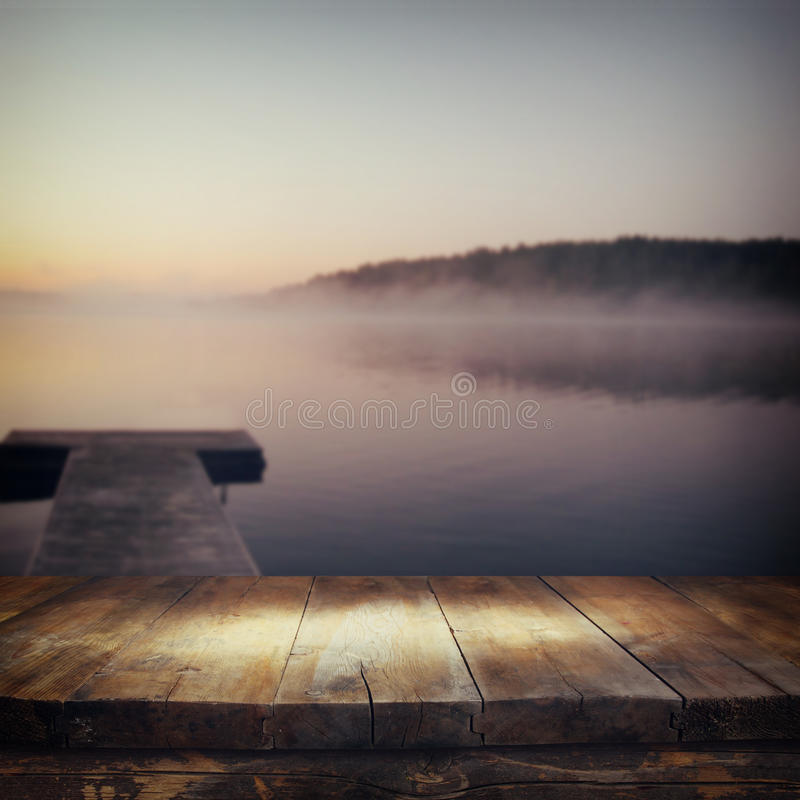 Vintage wooden board table in front of abstract photo of misty and foggy lake at morning sunrise. royalty free stock image