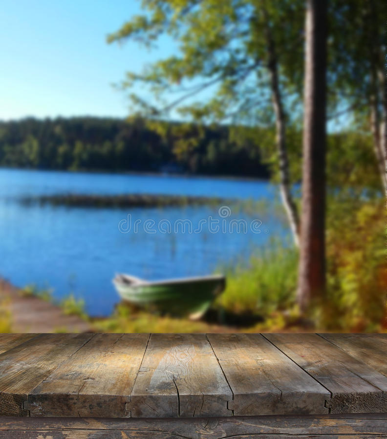 Vintage wooden board table in front of dreamy and abstract forest and lake landscape with lens flare. Vintage wooden board table in front of dreamy and abstract royalty free stock images