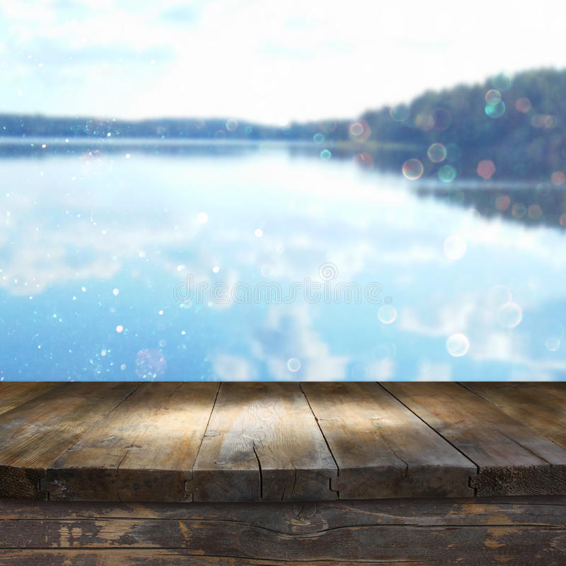 Vintage wooden board table in front of dreamy and abstract forest lake. Landscape with lens flare stock photography