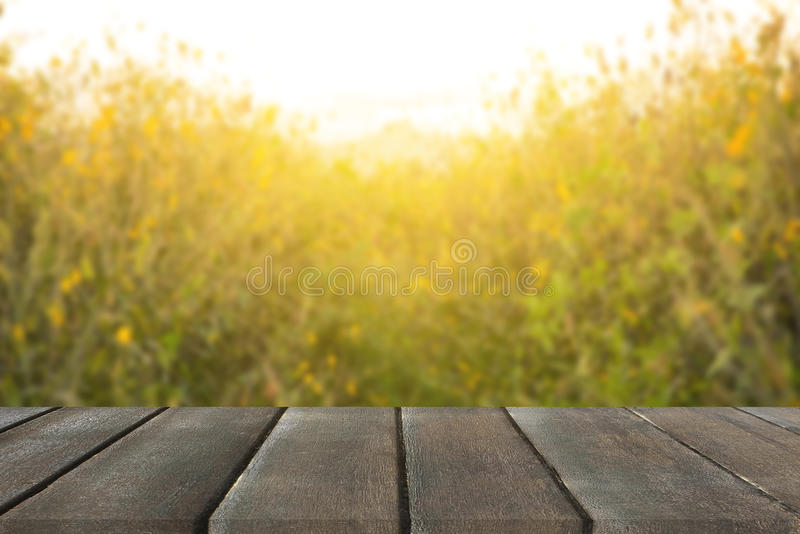 vintage wooden board table in front of dreamy and abstract yellow flower with lens flare stock image