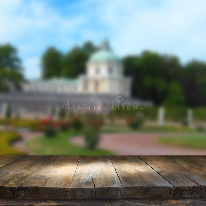 Vintage wooden board table in front of rustic counrty garden landscape.  stock photo
