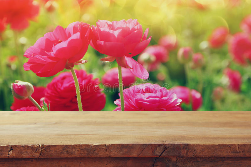 Vintage wooden board table in front of summer flowers field. product display and picnic concept.  stock images