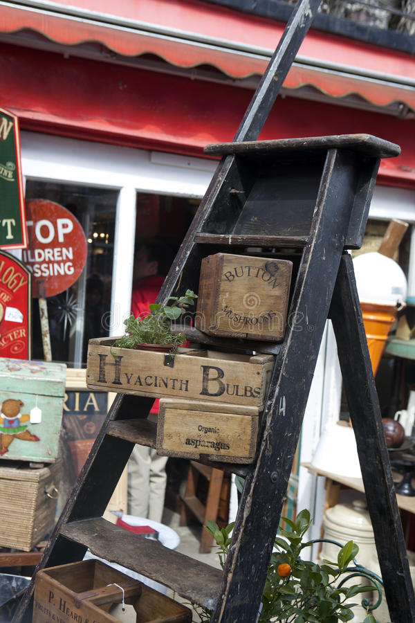 Vintage wooden boxes stand on a wooden staircase for sale on Portobello Road. LONDON, ENGLAND - JULY 12, 2017 Vintage wooden boxes stand on a wooden staircase stock image