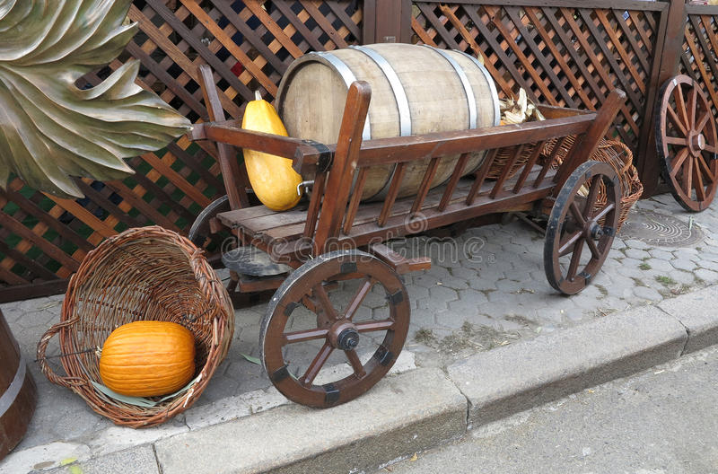 Vintage wooden cart with wine barrel, basket and pumpkin isolate. Vintage wooden cart with wine barrel, wicked basket and pumpkin isolated over white background royalty free stock photo