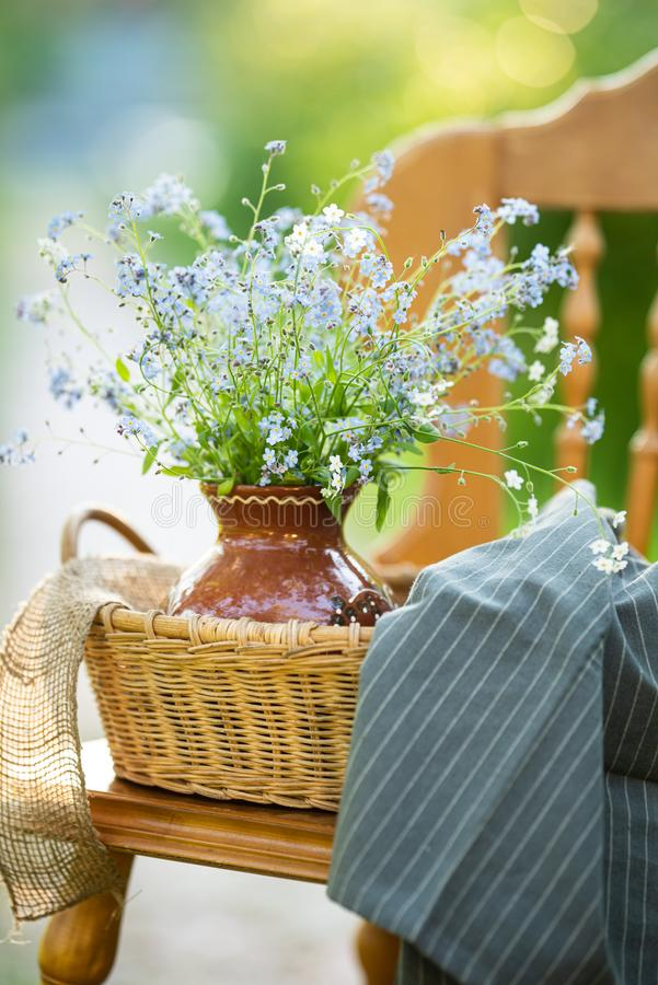 Vintage wooden chair with ceramic vase and bouquet of forget-me-not`s on it. Close up stock photos