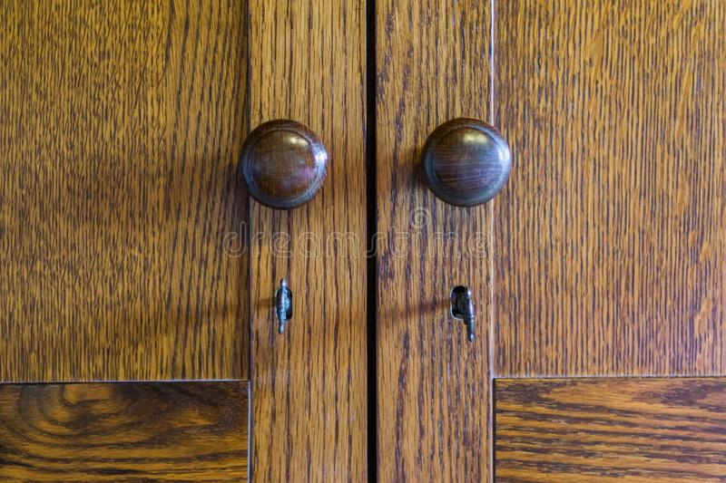 Vintage wooden closet doors of wardrobe with knobs and keys royalty free stock photos