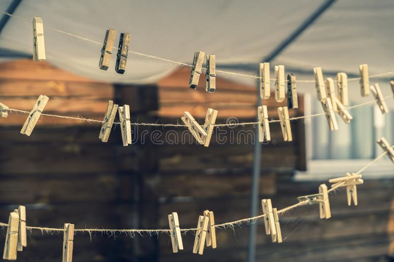 Vintage wooden clothespins on a natural rope. Several vintage wooden clothespins on a natural rope, countryside backdrop royalty free stock photography