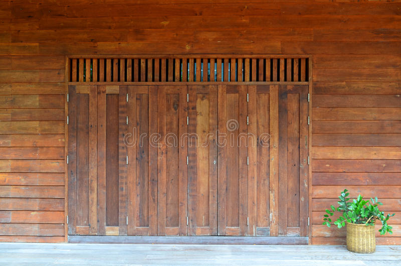 Vintage wooden door with green plant in wooven pot stock photography