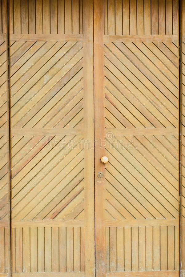 Vintage wooden door with shutters on a red brick wall stock image