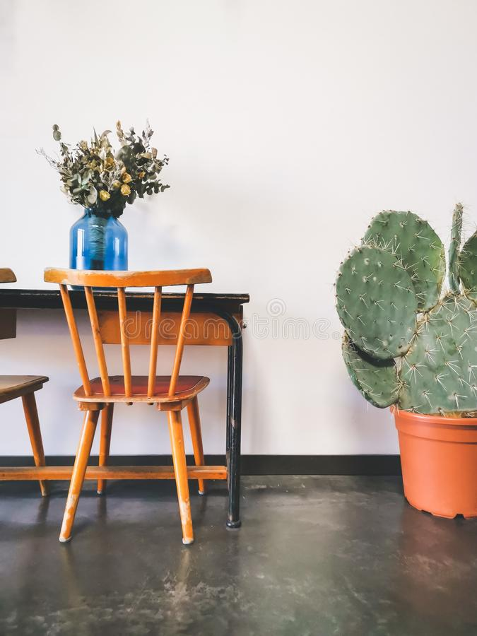 Vintage wooden elementary school desk with two wooden chairs, a dried flower arrangement in a blue vase against a white wall royalty free stock images