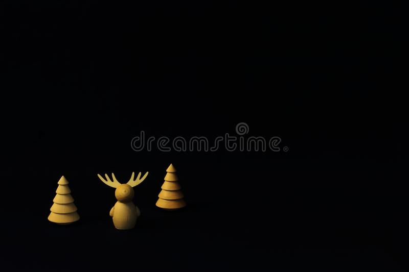 Vintage wooden figures of fir and deer on dark background. Symbolic concept - Christmas, family, gifts, New Year. Minimal style royalty free stock photo
