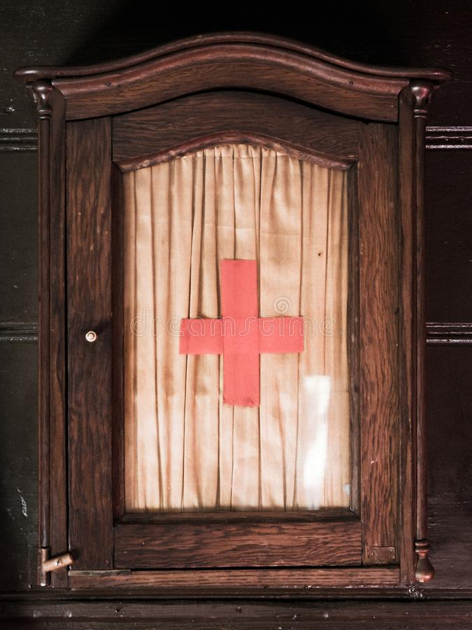 Vintage wooden first aid kit cabinet with glass door and red cross sign stock image