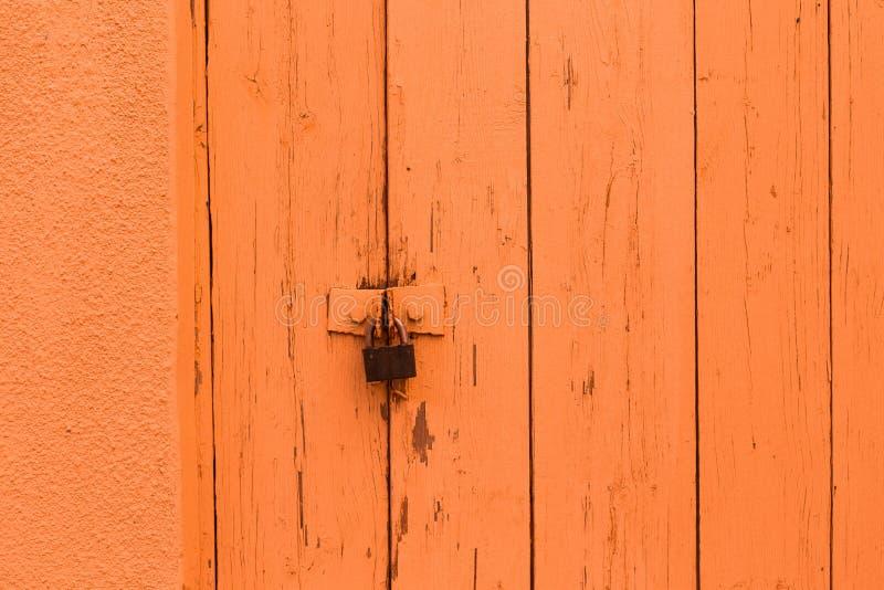 Vintage wooden gate retro padlock bright color. Vintage wooden gate with retro padlock painted in bright color background texture orange stock photo