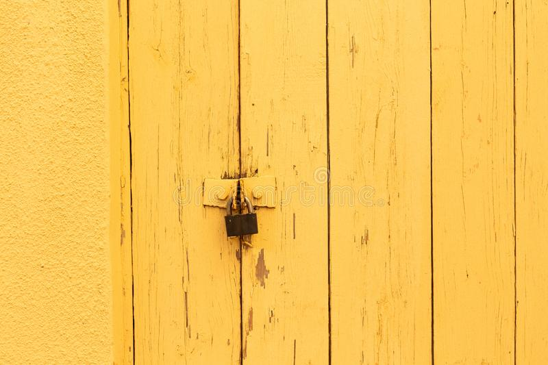 Vintage wooden gate retro padlock bright color. Vintage wooden gate with retro padlock painted in bright color background texture yellow royalty free stock images