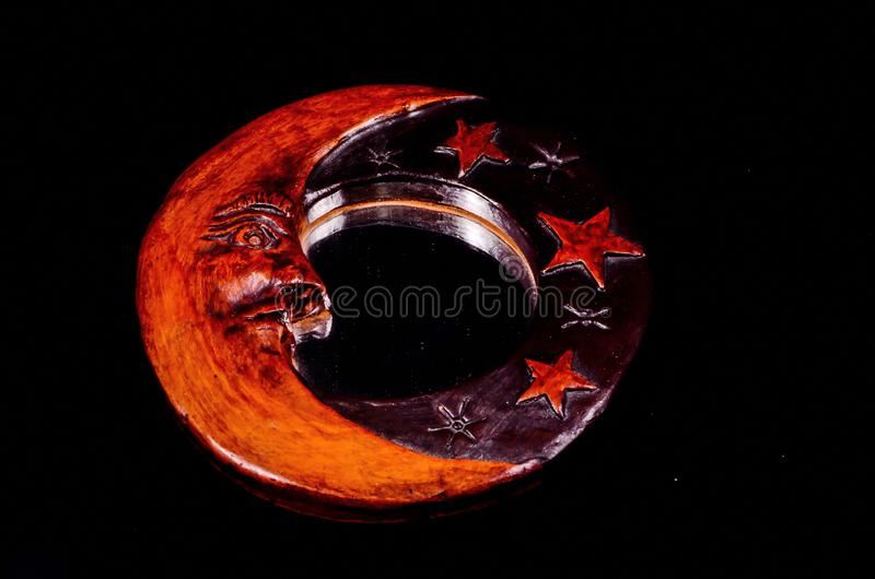 Vintage Wooden Handmade Mirror with Moon and Stars. On a Black Background royalty free stock photo