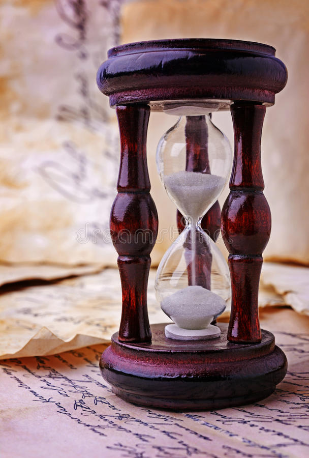 Vintage wooden hourglass and letters royalty free stock image