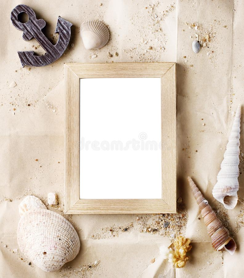 Vintage wooden photo frame on craft paper with sand and sea shells mock up royalty free stock images