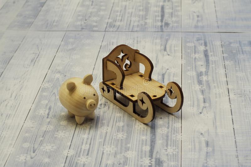 Vintage wooden sled and cheerful wooden pig on light background. Handmade. royalty free stock photo