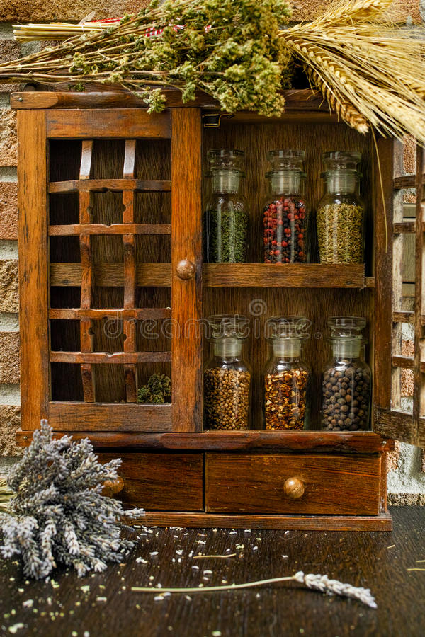 Vintage Wooden Spice Rack or Storage Cabinet and six glass bottles stock images