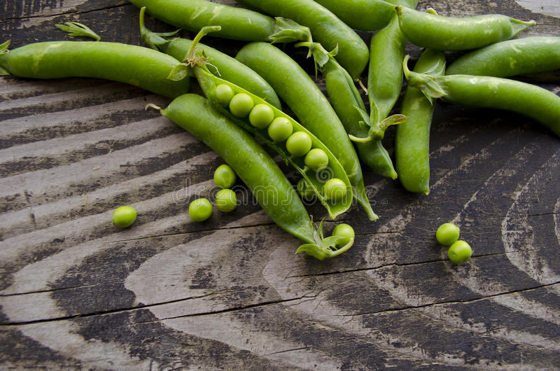 Vintage wooden surface for design with beautifully pods of green peas. Young fresh green peas on old wooden background. stock photos