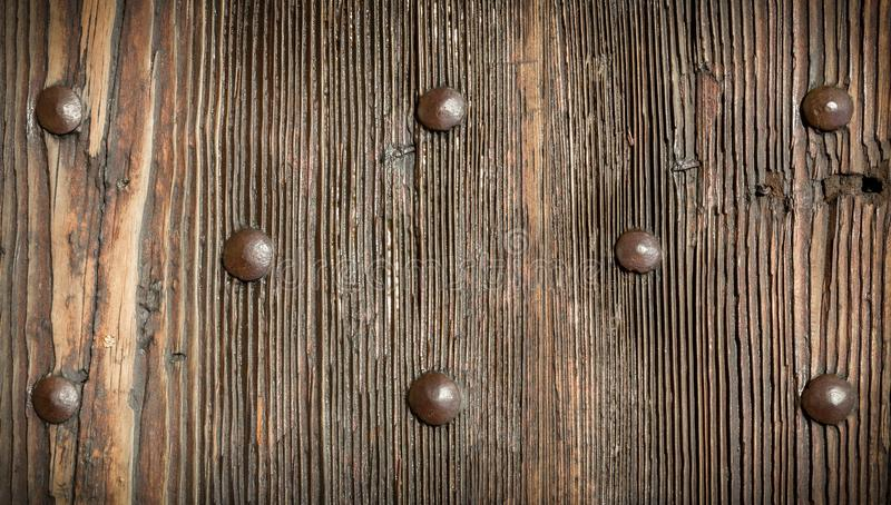 Fragment of a door with metal rivets. Vintage wooden texture with metal rivets, wood texture for background royalty free stock photo