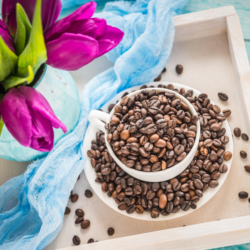 Vintage wooden tray with porcelain cup full of coffee beans and pink flowers on shabby chic mint background, top view.  stock photography