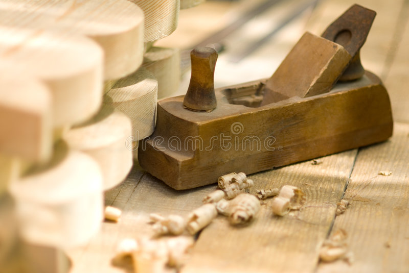 Vintage woodworking plane. Closeup of vintage woodworking plane with chips and planking royalty free stock photography