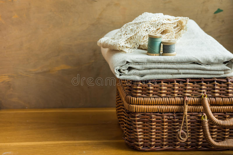 Vintage woven rattan crafts and sewing supply box, wooden spools, rolls of lace, folded linen fabric, aged wood background, hobby stock image