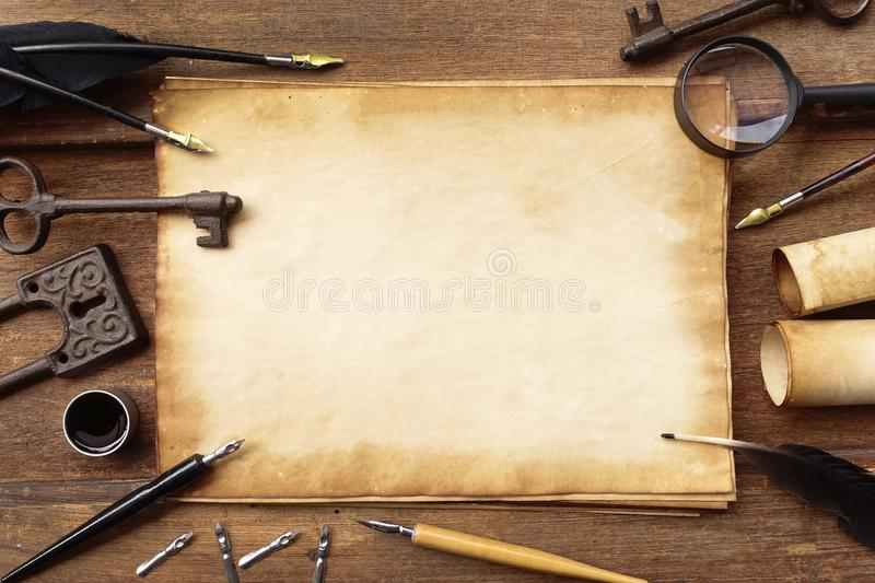 Vintage writing set with old paper on brown wood texture with feather and ink royalty free stock image