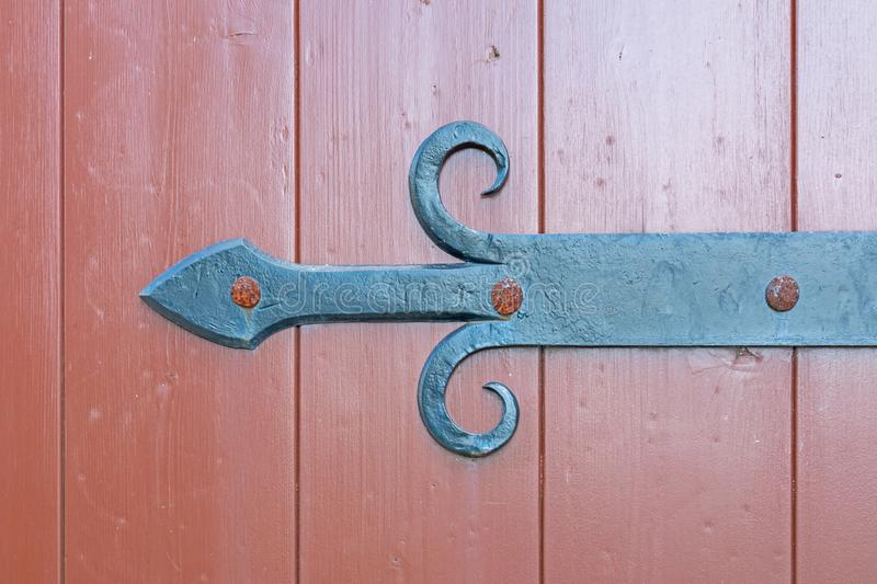 Vintage wrought iron bracket in the form of an arrow to a wooden gate 19th century royalty free stock image
