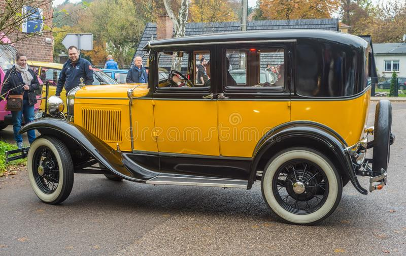 Vintage classic yellow black Ford A driving. Ancient classic yellow and black Ford A of 1930 beutifully restored driving at veteran cars meeting in Gdansk Oliwa royalty free stock photo