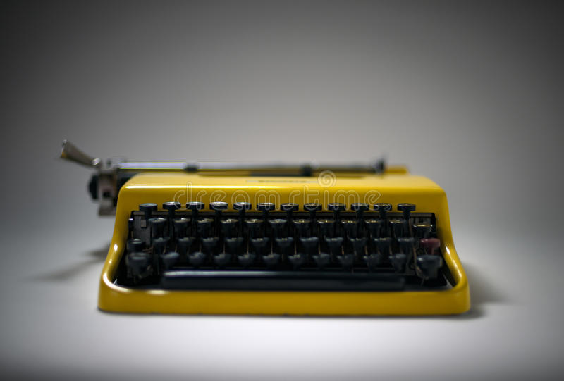 Vintage yellow typewriter in evocative spotlight royalty free stock image