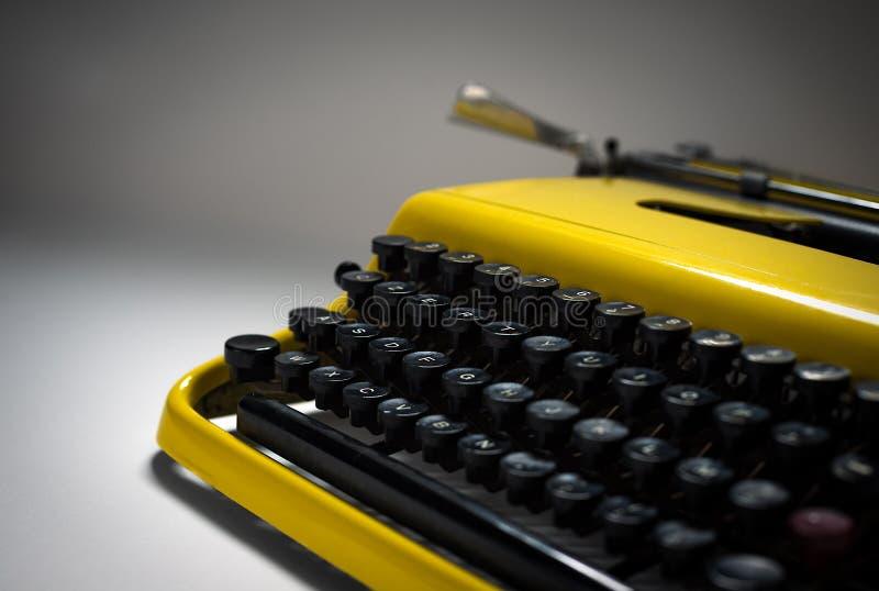 Vintage yellow typewriter in evocative spotlight stock image