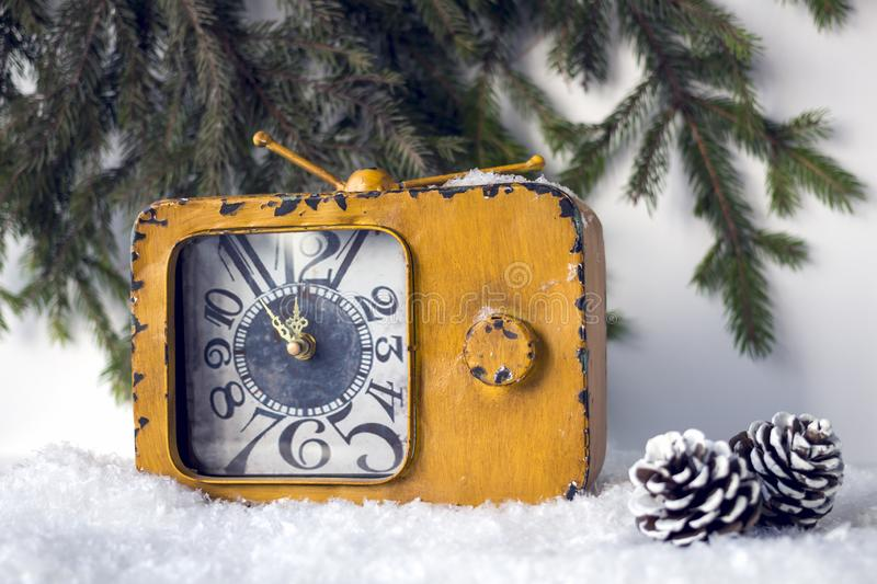 Vintage  yellow watch in the snow on a background of fir branches. royalty free stock photos