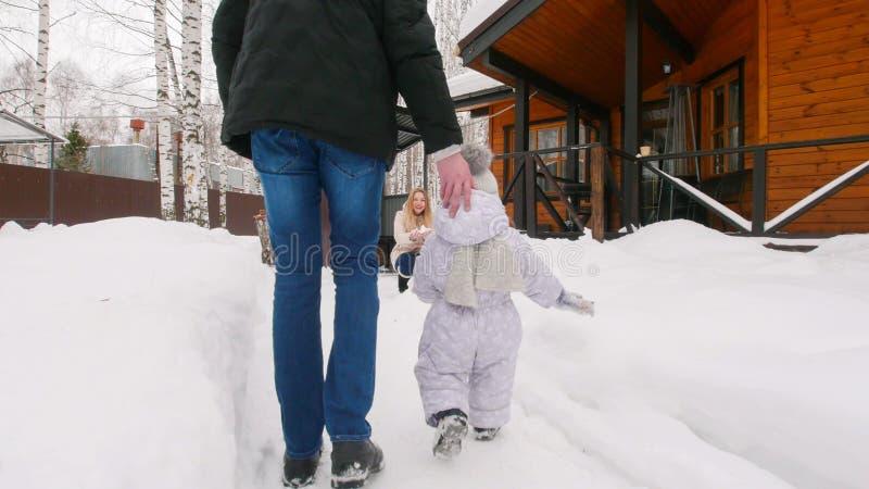 Vinter Den unga familjen som går med deras, behandla som ett barn på borggården Behandla som ett barn går till hans moder royaltyfria foton