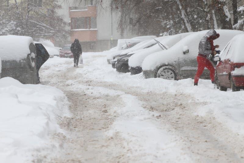 Vinter Folket går på en mycket snöig trottoar och väg Folket kliver på en iskall bana, iskall trottoar Uncleaned gator och vägar royaltyfri bild