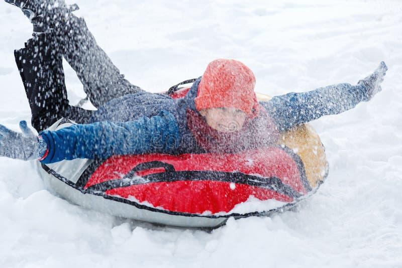 Vinter, fritid och underhållningbegrepp den gulliga unga pojken i lekar för blått omslag med snö, har gyckel, leenden Tonåringen  royaltyfri fotografi