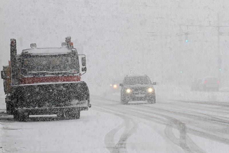 Vinter Snöplogen gör ren vägen i staden under en enorm snöstorm, snörengöringmaskin på boulevarden med bilar i stort snöfall arkivfoton
