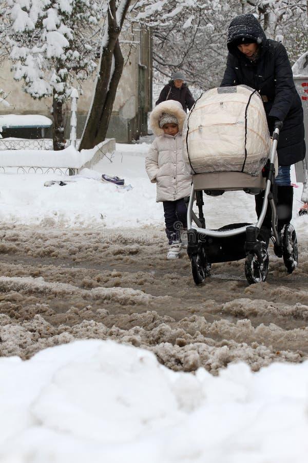 Vinter is snow Folket går hårt på en snöig iskall väg som passerar snöig bilar på den uncleaned iskalla gatan efter ett tungt snö arkivfoton