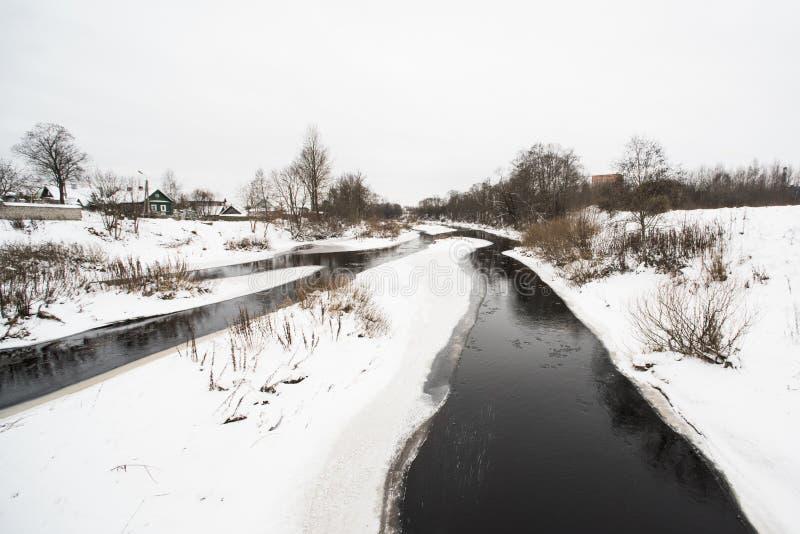 Vinterdaglandskap med snö, floden, träd och det lantliga huset royaltyfria foton