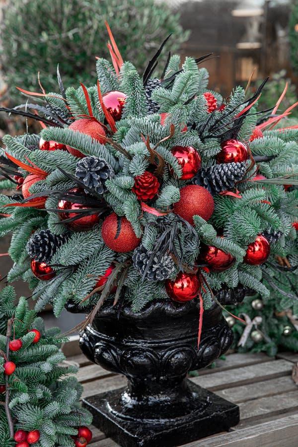 Vinterdekanter Vackra arrangemang av julgranarnas röda bollar, koner, naturliga grusgrenar för inomhusbruk arkivbilder