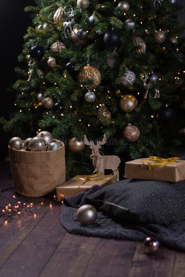 Vinterdekor: Julgran, girland, bollar, gåvor och hemtrevliga randiga och gråa pläd med kuddar royaltyfri foto