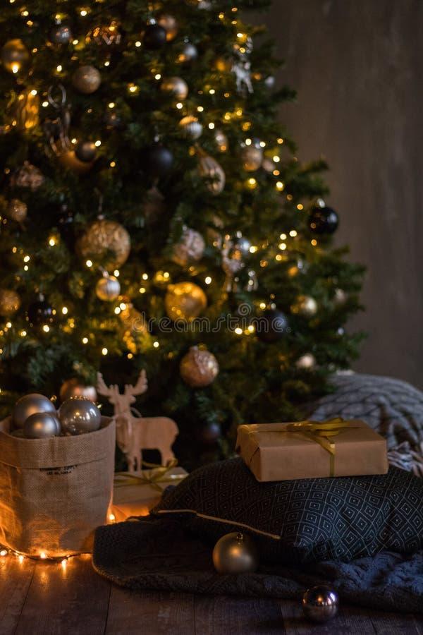Vinterdekor: Julgran, girland, bollar, gåvor och hemtrevliga randiga och gråa pläd med kuddar Utvalt fokusera arkivbild