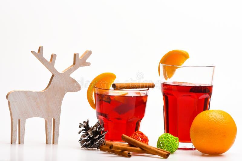 vinterdryckbegrepp Exponeringsglas med funderat vin eller den varma drinken nära trähjortgarnering och kotte på vit bakgrund royaltyfri fotografi