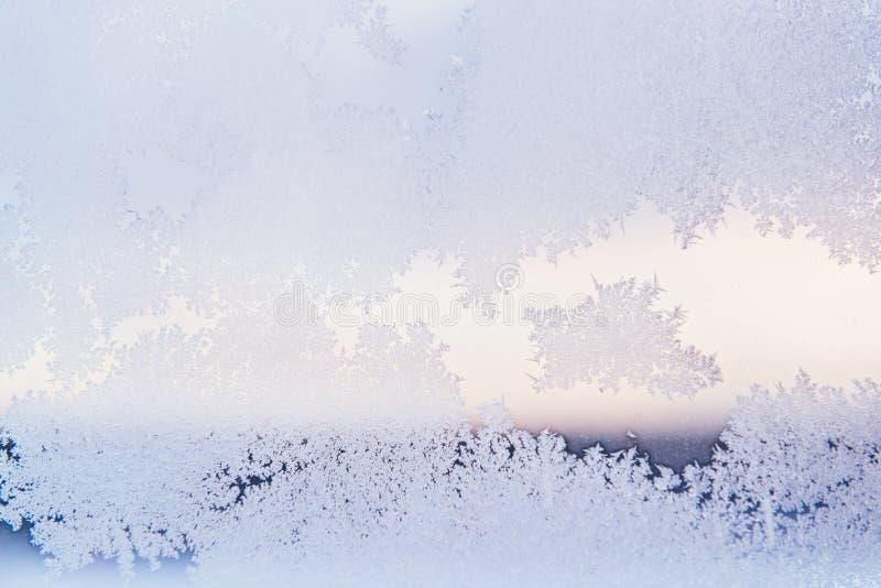 Vinterfönstret förser med rutor bestrukna skinande iskalla frostmodeller close upp Vinterväder arkivbild