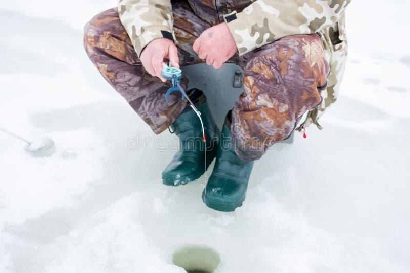 Vinterfiske på is Fiskare i kamouflagelikformig som sitter på en ask på is som rymmer en fiskeisstång för vinterfiske som är låg arkivfoto
